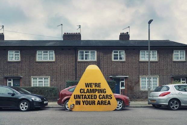 "Image of car parked in a street with a giant clamp on it which says ""We're clamping untaxed cars in your area"""