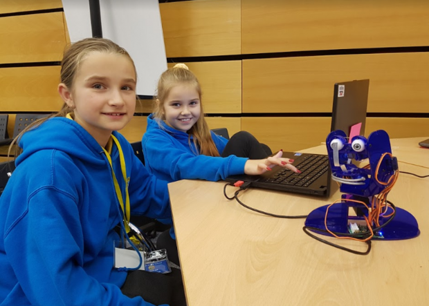 Two girls from Clase Primary School using a laptop to program a robot