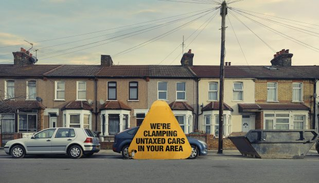 Giant clamp with 'We're clamping untaxed cars in your area' on it on a car in front of row of terraced houses
