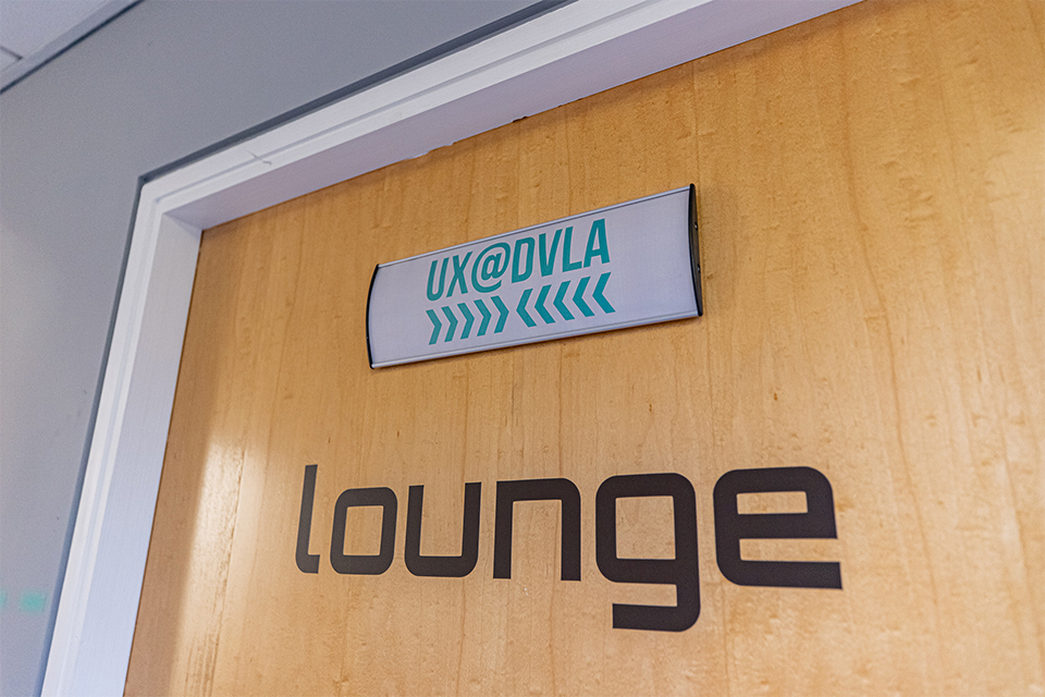 Door with a UX@DVLA sign at the top of it, and a lounge sign underneath.